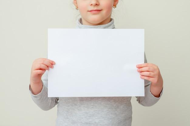 Feuille de papier vierge dans les mains de l'enfant