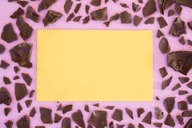 Feuille de papier vierge avec du chocolat fissuré sur la table