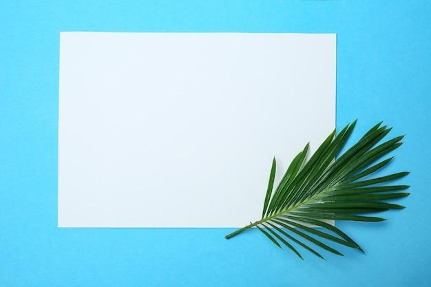 Feuille de papier vierge avec des feuilles tropicales sur fond de couleur