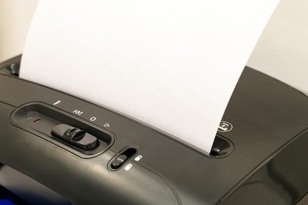 Une feuille de papier vierge insérée dans la déchiqueteuse à détruire pour des raisons de sécurité