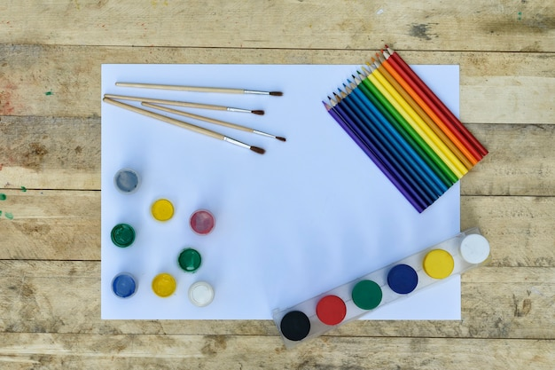 Feuille de papier vierge, peinture, pinceaux et crayons de couleur