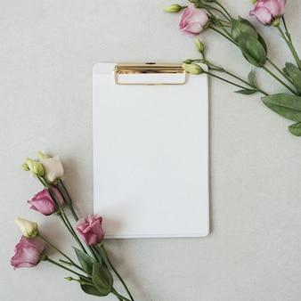 Feuille de papier vierge presse-papiers cadre de fleurs roses