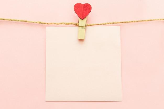 Feuille de papier vierge rose sur une corde à linge et des pinces à linge avec coeur rouge sur un rose