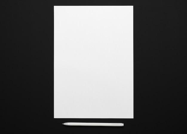 Une feuille de papier vierge et un stylo sur une table noire, vue de dessus - modèle pour tout texte ou inscription