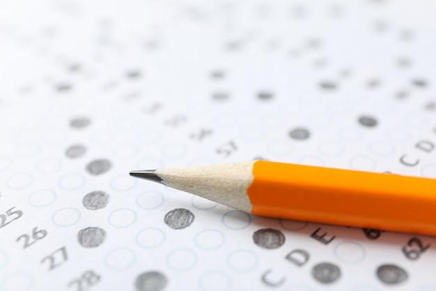 Feuille de pointage de test avec réponses et crayon, gros plan