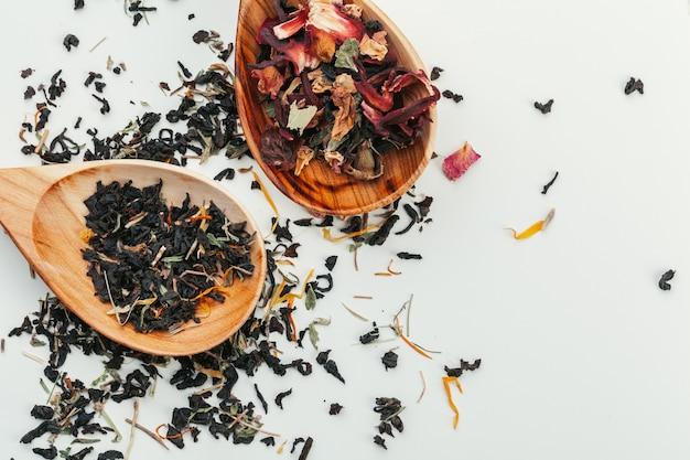 Feuille de thé dans une cuillère en bois isolée