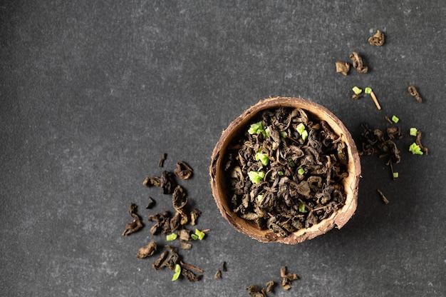 Feuille de thé vert sec avec des fruits sausep dans un bol de noix de coco avec des feuilles éparses, fond gris, gros plan, vue de dessus