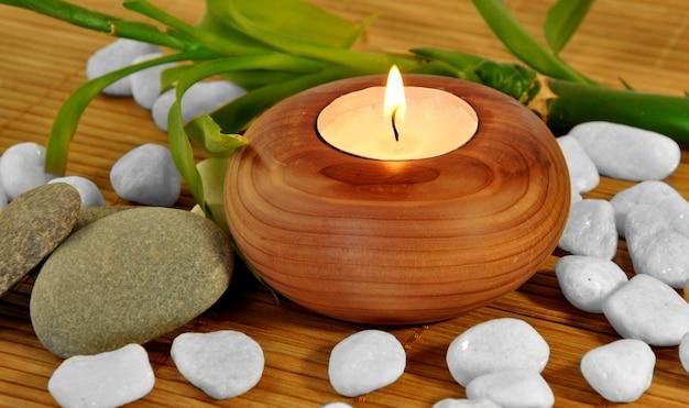 Feuille verte avec de l'eau naturelle tombe des bougies avec des pierres de couleur