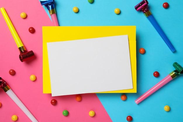 Feuille vide, sifflets d'anniversaire et bonbons sur fond bicolore, espace pour le texte