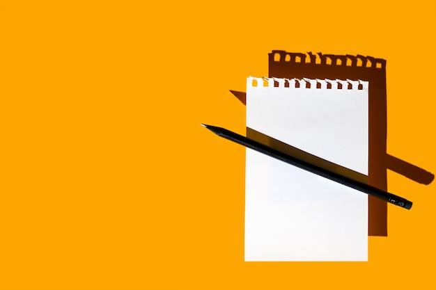 Une feuille vierge de bloc-notes, un crayon noir et des ombres dures sur jaune vif