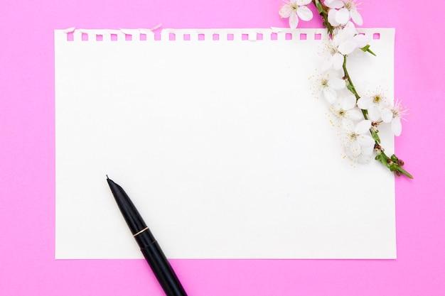 Feuille vierge de bloc-notes avec espace de copie. a proximité un stylo à encre, une branche de fleurs sur fond rose. concept de printemps pour vos textes.