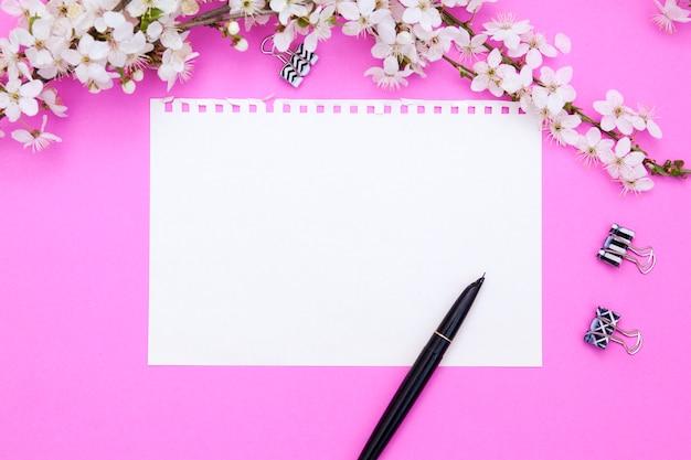 Feuille vierge de bloc-notes avec espace de copie. a proximité un stylo à encre, des reliures, une branche de fleurs sur fond rose. concept de printemps pour vos textes.