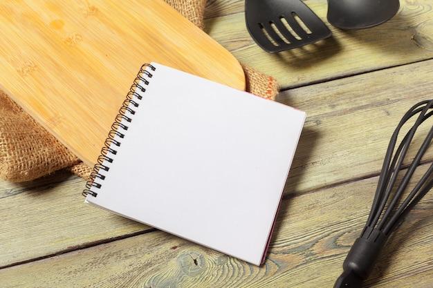 Feuille vierge de bloc-notes ouvert et ustensiles de cuisine sur table avec nappe, espace copie