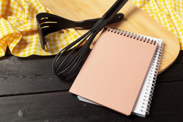 Feuille vierge de bloc-notes ouvert et ustensiles de cuisine sur la table