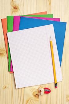 Feuille vierge de cahier d'école, crayon et taille-crayon sur table en bois
