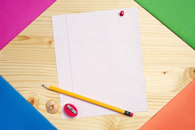 Feuille vierge de cahier d'école, crayon et taille-crayon