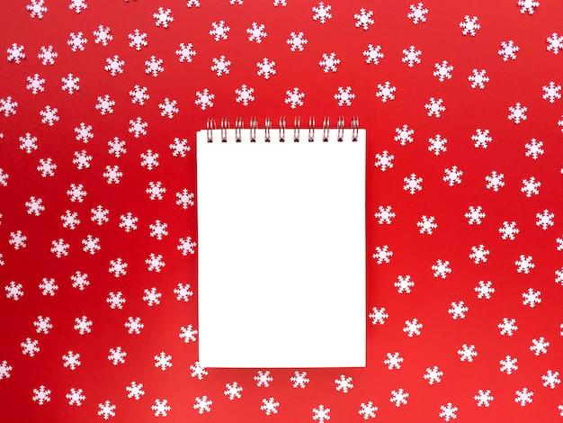 Feuille vierge de cahier avec des flocons de neige blancs dispersés sur fond rouge. concept éducatif. mise à plat simple avec espace de copie.