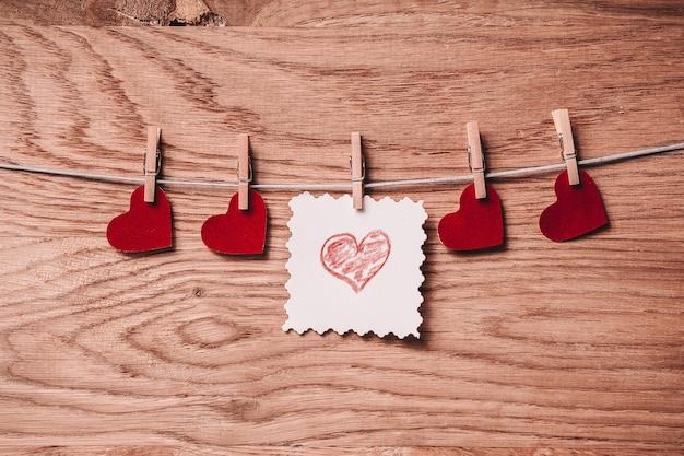 Feuille vierge et coeurs sur pinces à linge sur fond en bois. photo avec espace copie