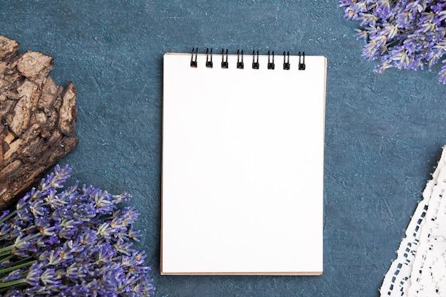Une feuille vierge d'ordinateur portable plat avec de la lavande, de la dentelle, de l'écorce. rédigez votre message