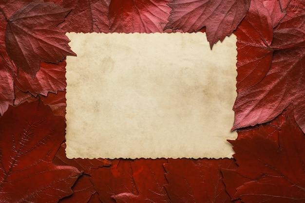 Une feuille de vieux papier sur fond de feuilles d'automne rouges. espace pour le texte. fond d'automne. mise à plat.