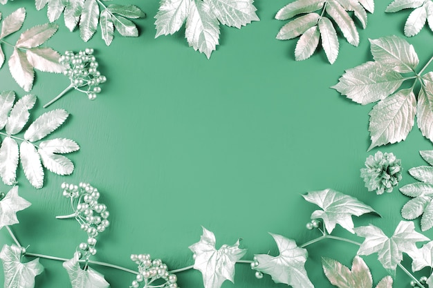 Feuilles d'argent sur fond de menthe verte, espace copie, vue de dessus
