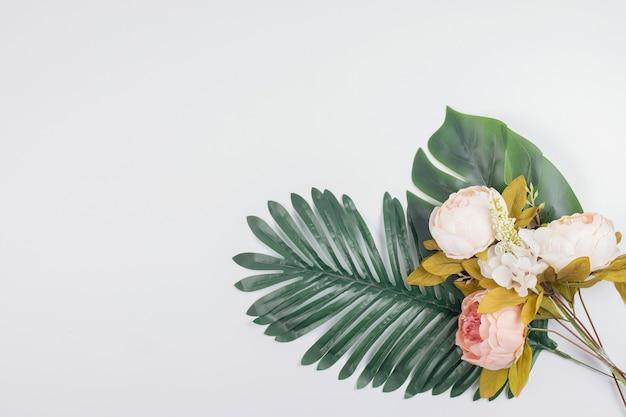 Feuilles artificielles et fleurs de pivoine.