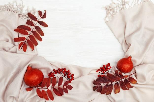 Feuilles automnales rouges de sorbier, de sorbier et de petite décoration jaune pampkin, écharpe en tissu confortable sur fond en bois blanc avec espace de copie. vue aérienne. thème d'automne.