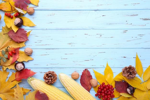 Feuilles d'automne avec des baies et des légumes sur un fond bleu
