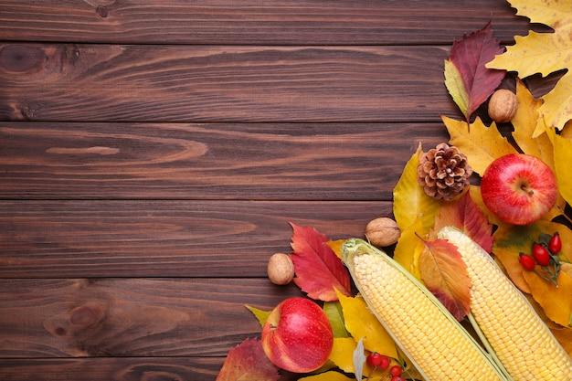 Feuilles d'automne avec des baies et des légumes sur fond marron