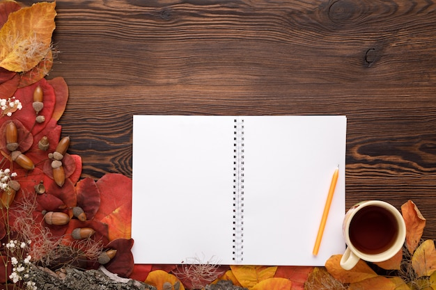 Feuilles d'automne, biscuits et cahier papier sur bois