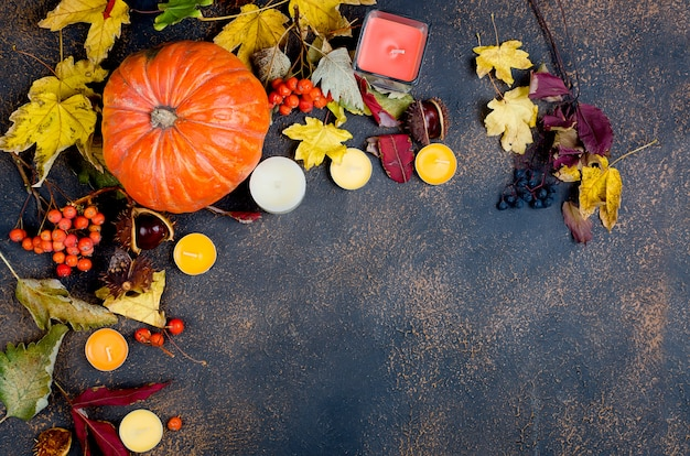 Feuilles d'automne, citrouille, châtaignes, bougies sur un fond sombre