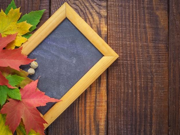 Feuilles d'automne colorées avec cadre en bois pour texte sur un bois texturé