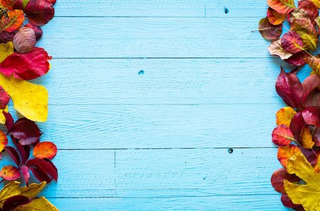 Feuilles d'automne colorées, sur un fond de cadre en bois