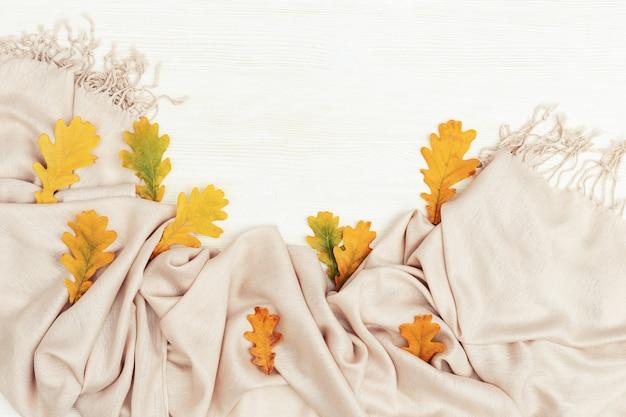 Feuilles d'automne jaune vif à plat sur un fond en bois blanc avec espace de copie. beaucoup de feuilles de chêne et palantine chaleureuse et chaleureuse, thème automnal. vue de dessus.