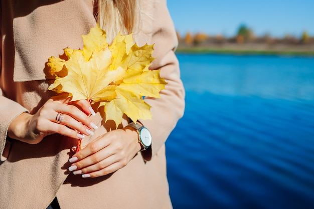 Feuilles d'automne. jeune femme marchant au bord du lac et tenant des feuilles d'érable jaune