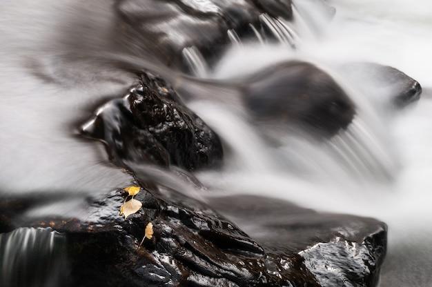 Feuilles d'automne sur les pierres de la cascade. prise de vue longue exposition. beau paysage d'automne