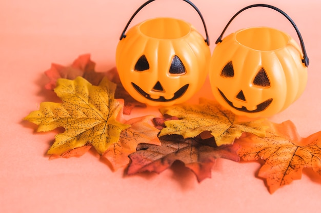 Feuilles d'automne près des paniers de jack-o-lantern