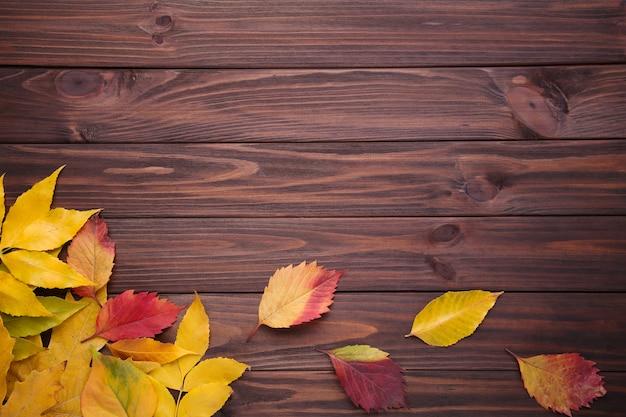Feuilles d'automne rouge et orange sur une table marron