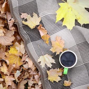 Feuilles d'automne et tasse de café fumant chaud se trouve sur le plaid à carreaux à l'extérieur