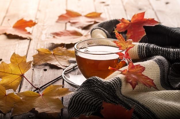 Feuilles d'automne et tasse de thé sur la table en bois.