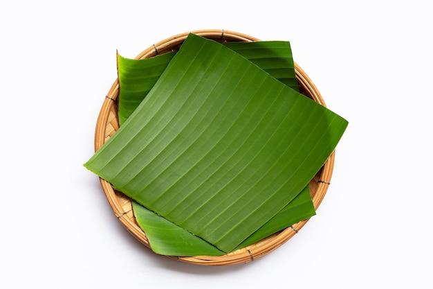 Feuilles de bananier dans un panier de bambou sur fond blanc.