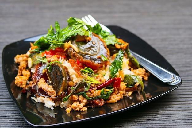 Feuilles de basilic avec porc haché et œuf confit