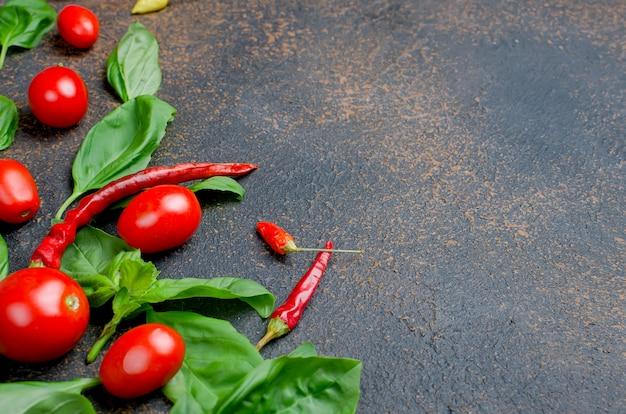 Feuilles de basilic vert, tomates cerises et épices au poivre