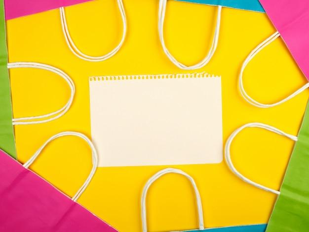 Feuilles blanches vierges et sacs en papier multicolores