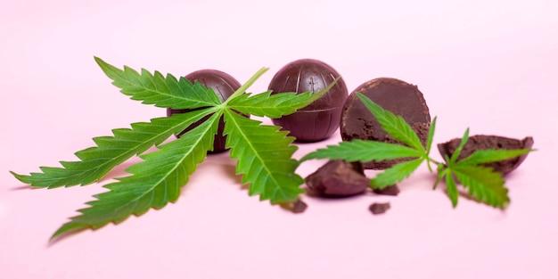 Feuilles de cannabis et bonbons sur fond rose