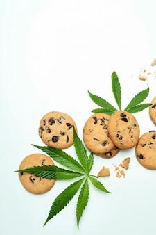 Feuilles de cannabis et cookies sur fond blanc