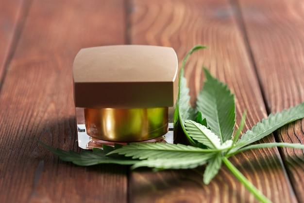 Feuilles de cannabis et huile sur fond de bois