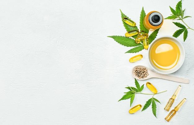 Feuilles de capsules d'huile de cbd et graines de cannabis sur une table en béton gris