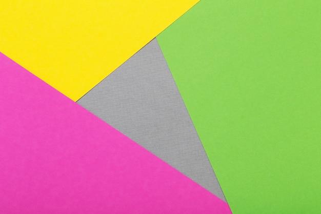 Feuilles de carton gris, jaune et vert et rose fond géométrique
