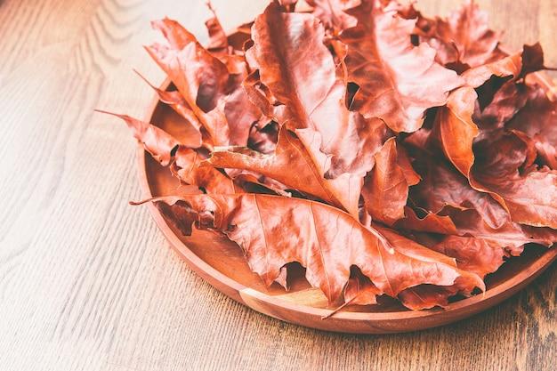 Feuilles de chêne rouge dans une assiette en bois sur une table